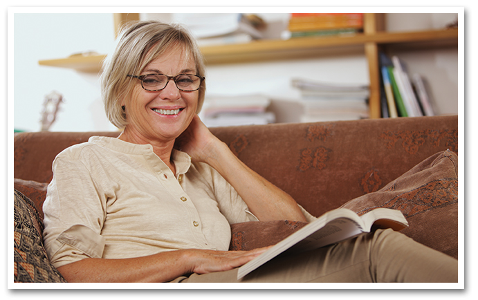 Smiling older woman on couch reading
